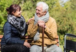 Middle-aged daughter with her elderly father enjoying eachother's company, laughing together, on a beautiful sunny day in the park.