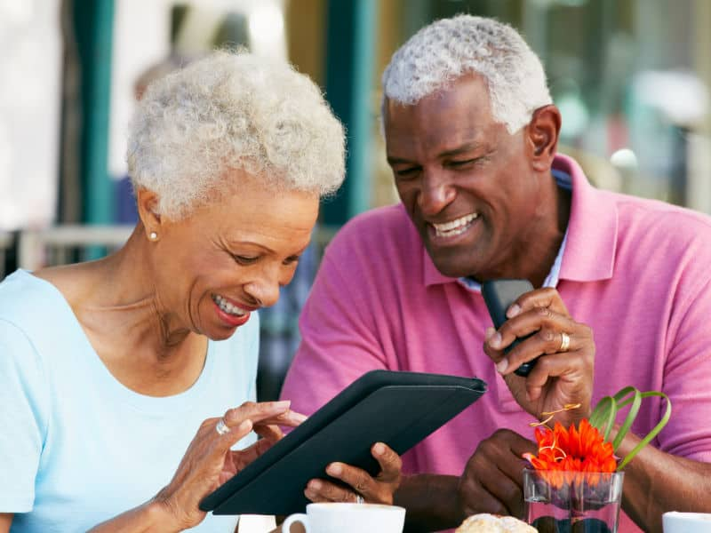 Happy couple looking at National Senior Advisors online